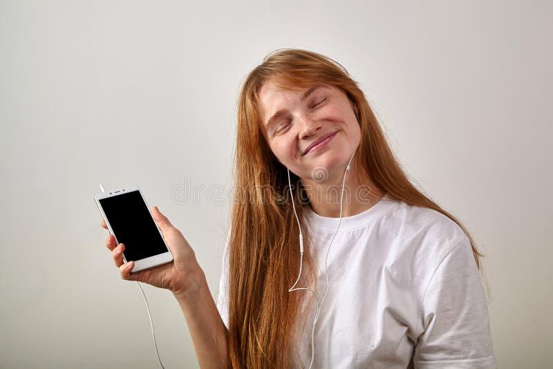 Portrait de jeune fille à tête rouge avec des taches de rousseur tenant le téléphone image libre de droits