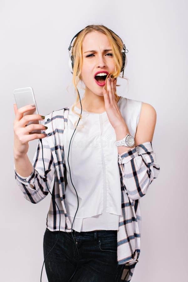 Portrait de jeune fille émotive élégante dans des vêtements sport à la mode tenant la main près du visage et lisant le message mi image stock