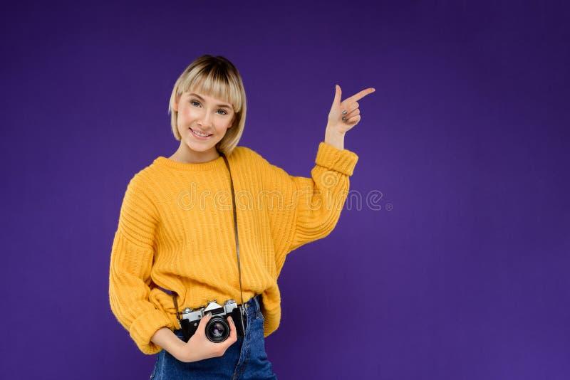Portrait de jeune fille avec l'appareil-photo au-dessus du fond pourpre photographie stock libre de droits