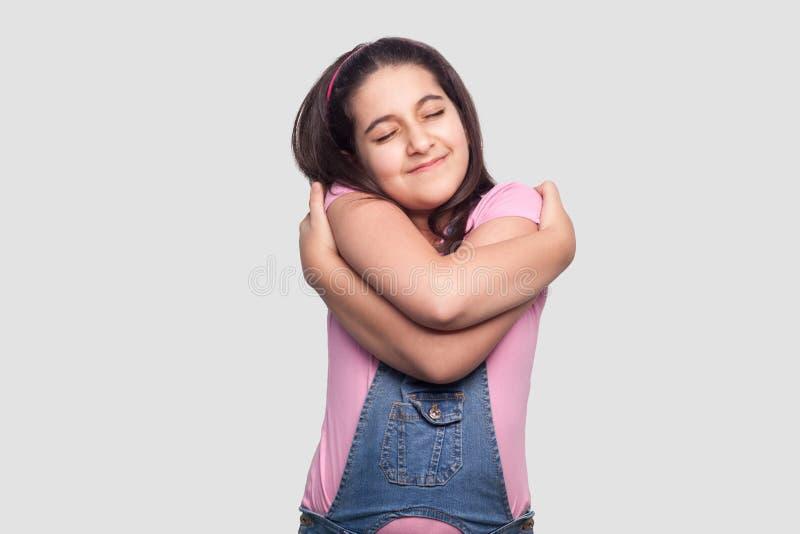 Portrait de jeune fille de belle brune satisfaisante heureuse dans le T-shirt rose occasionnel et la position bleue de combinaiso photographie stock libre de droits