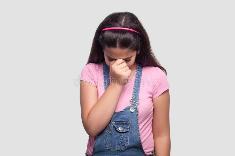 Portrait de jeune fille de belle brune triste dans le style occasionnel, le T-shirt rose et la position bleue de combinaisons de  images libres de droits