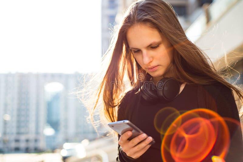 Portrait de jeune fille de brune d'adolescent avec de longs cheveux fille sur la ville dans la robe noire regardant au téléphone  photos libres de droits