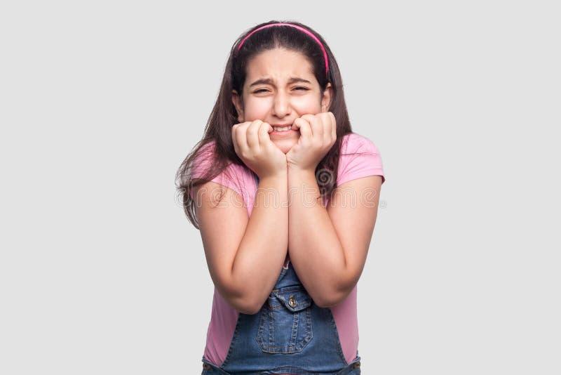 Portrait de jeune fille de brune triste nerveuse d'alonel dans le T-shirt rose et des combinaisons bleues de denim se tenant avec photos libres de droits