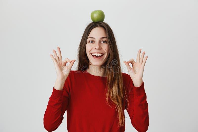 Portrait de jeune fille caucasienne attirante avec le sourire fantastique et le regard heureux, montrant le geste correct avec le images stock