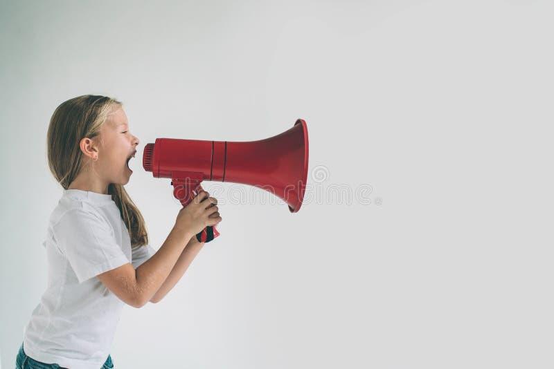 Portrait de jeune fille criant utilisant le mégaphone au-dessus du fond Chil dans la chemise blanche, tir de studio photos stock