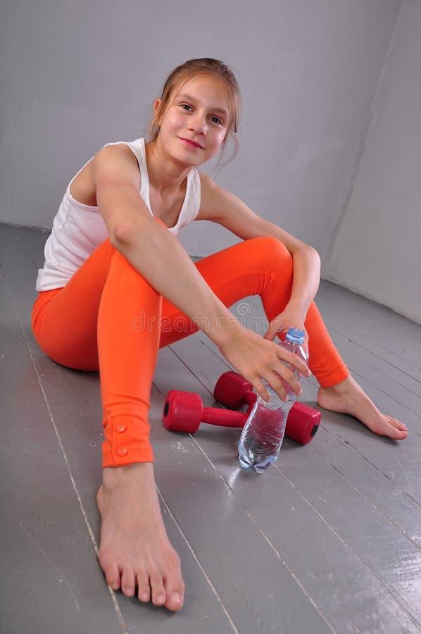 Portrait de jeune fille de l'adolescence folâtre avec une bouteille d'eau potable  photos libres de droits