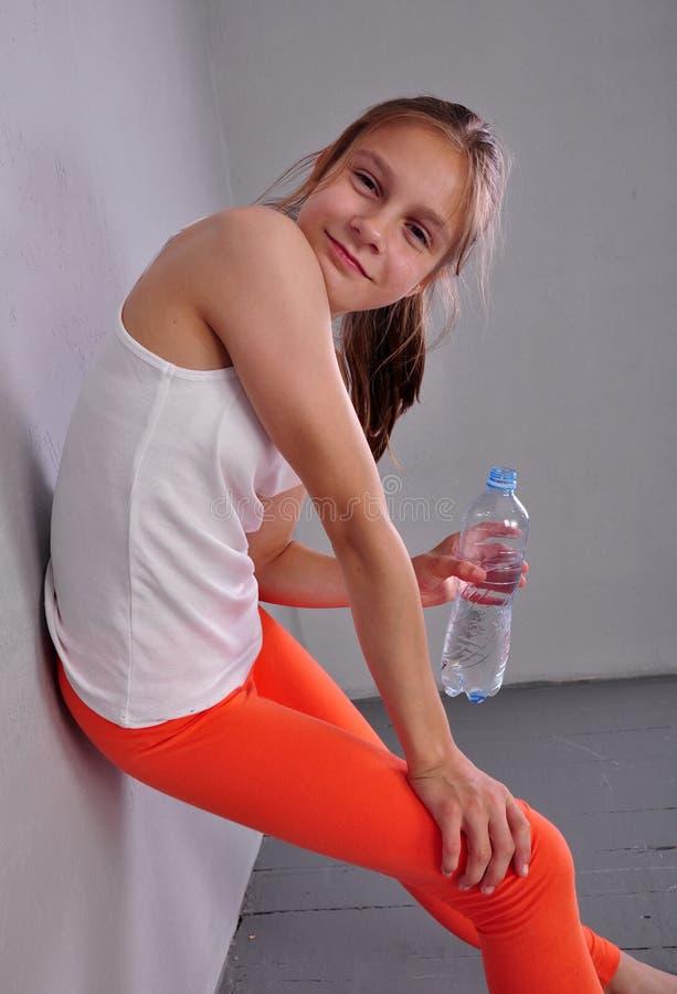 Portrait de jeune fille de l'adolescence folâtre avec une bouteille d'eau potable  image stock