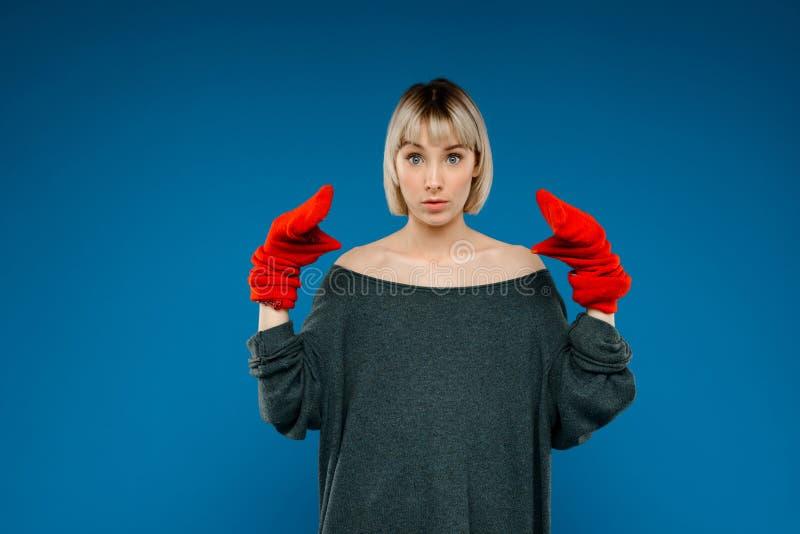 Portrait de jeune fille dupant dans les gants au-dessus du fond bleu image libre de droits