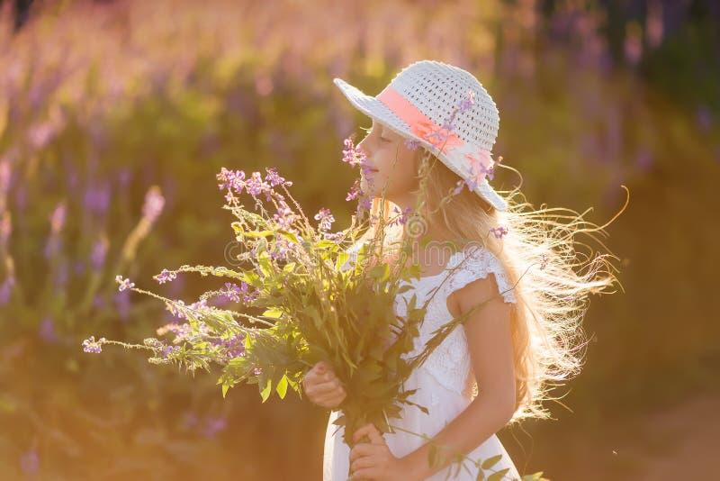 Portrait de jeune fille mignonne avec de longs cheveux dans un chapeau au coucher du soleil i images libres de droits