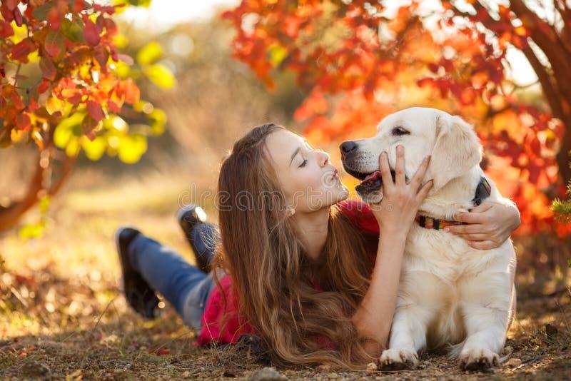 Portrait de jeune fille se reposant au sol avec son chien d'arrêt de chien dans la scène d'automne photos stock