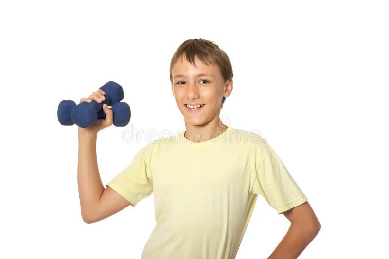 Portrait de jeune garçon faisant des exercices avec des haltères d'isolement sur le fond blanc images libres de droits