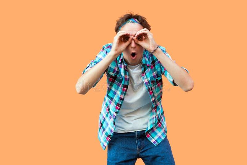 Portrait de jeune homme étonné dans la position à carreaux bleue occasionnelle de chemise et de bandeau avec le geste de mains de image libre de droits