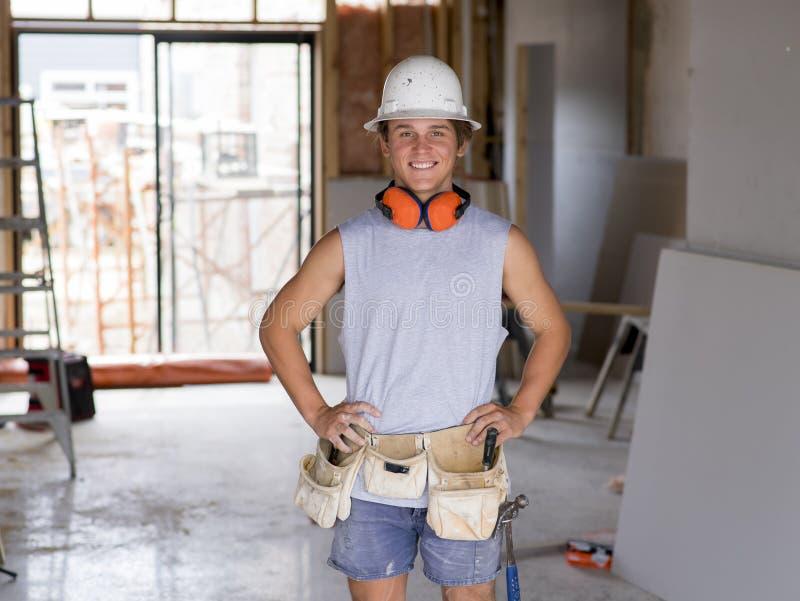 Portrait de jeune homme attirant de constructeur sur son 20s posant sûr et fier heureux au helme de port de protection de chantie image libre de droits