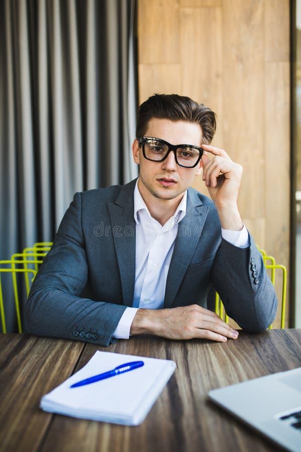 Portrait de jeune homme attirant en verres se reposant au bureau avec l'ordinateur portable photographie stock libre de droits