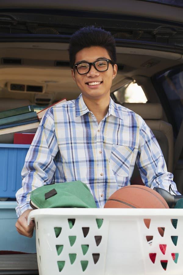 Portrait de jeune homme avec des articles de dortoir d'université derrière la voiture, regardant l'appareil-photo image stock