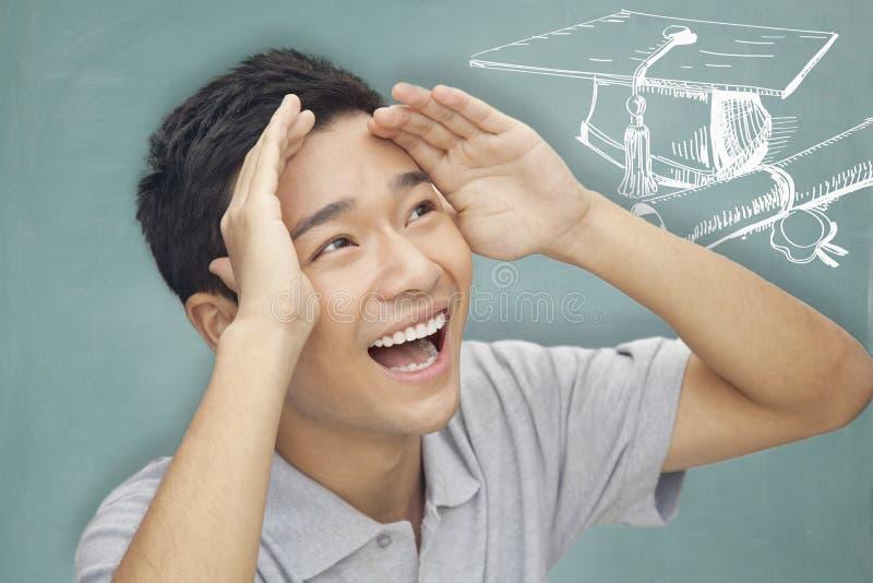 Portrait de jeune homme avec des bras augmentés et regardant à l'avenir, à l'obtention du diplôme et à l'éducation photo libre de droits