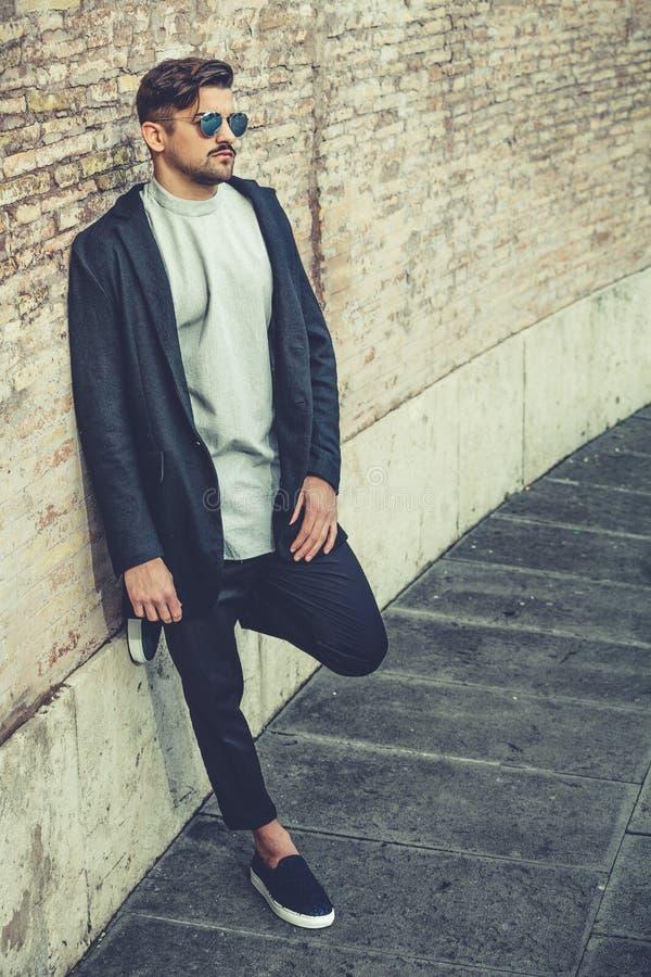Portrait de jeune homme avec du charme avec des lunettes de soleil dehors image libre de droits