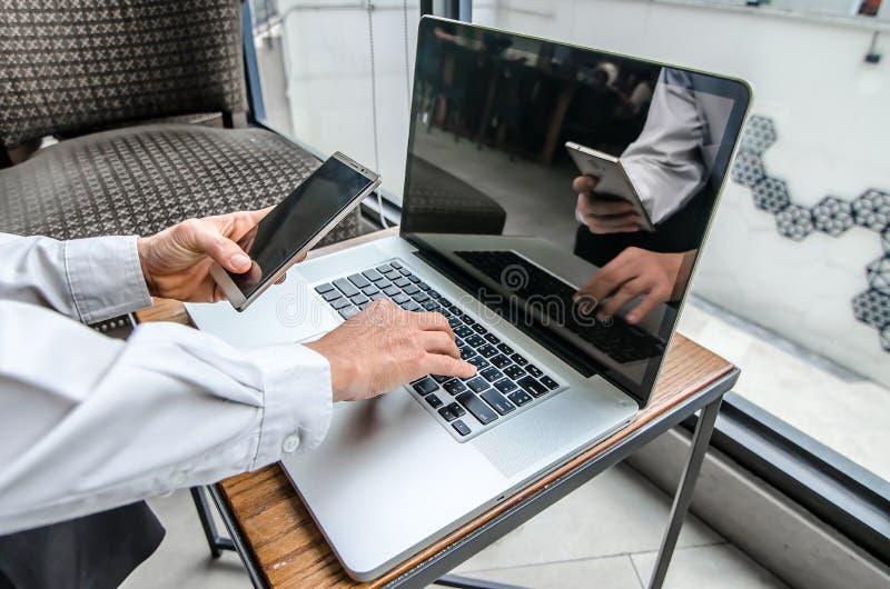 Portrait de jeune homme avec le téléphone portable travaillant sur l'ordinateur portable images stock