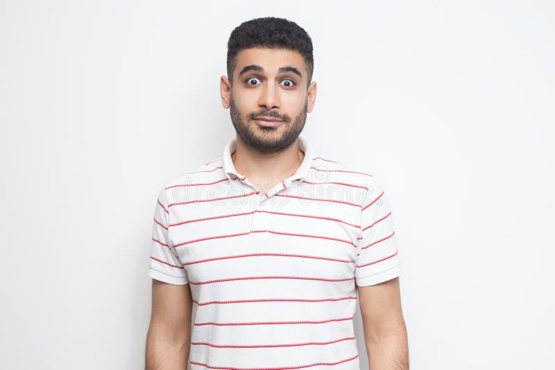 Portrait de jeune homme barbu beau étonné la position rayée de T-shirt avec de grands yeux et en regardant la caméra photos libres de droits