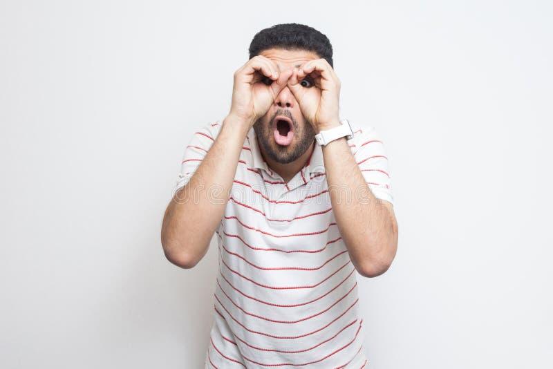 Portrait de jeune homme barbu beau drôle étonné dans la position rayée de T-shirt avec le geste de mains de jumelles sur des yeux image libre de droits