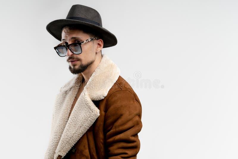 Portrait de jeune homme barbu dans le chapeau noir et le manteau brun dans des lunettes de soleil noires d'isolement au-dessus du photo stock