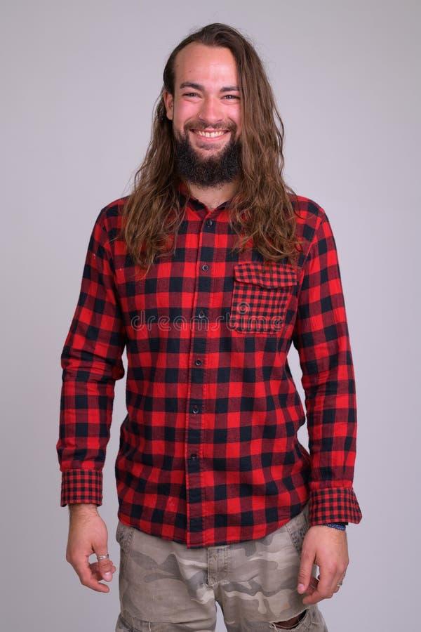 Portrait de jeune homme barbu heureux de hippie avec le long sourire de cheveux photo stock