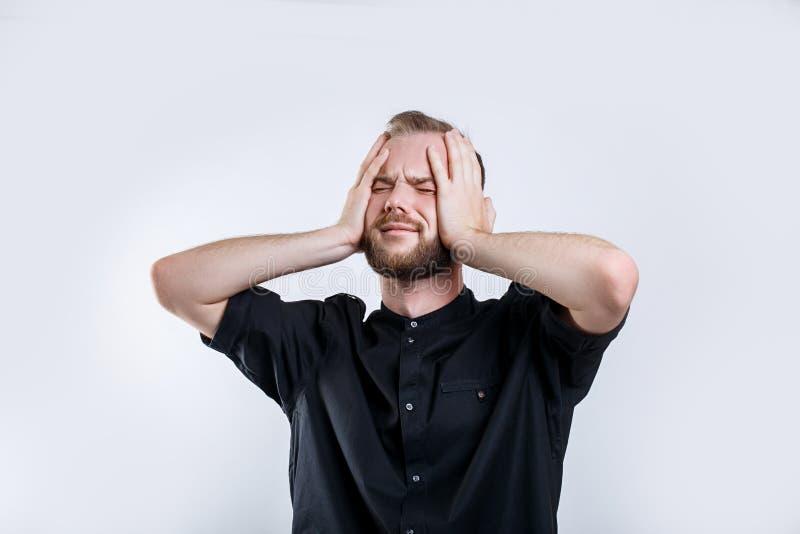 Portrait de jeune homme barbu inquiété avec les yeux fermés Jeune homme d'affaires chargé photo libre de droits