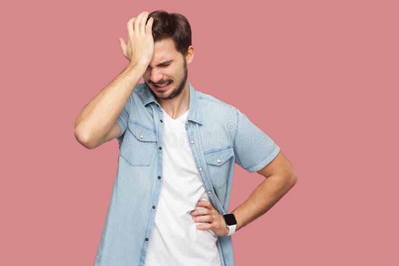 Portrait de jeune homme barbu de seul perdant triste dans la position bleue de chemise de style occasionnel maintenant sa tête et photos libres de droits