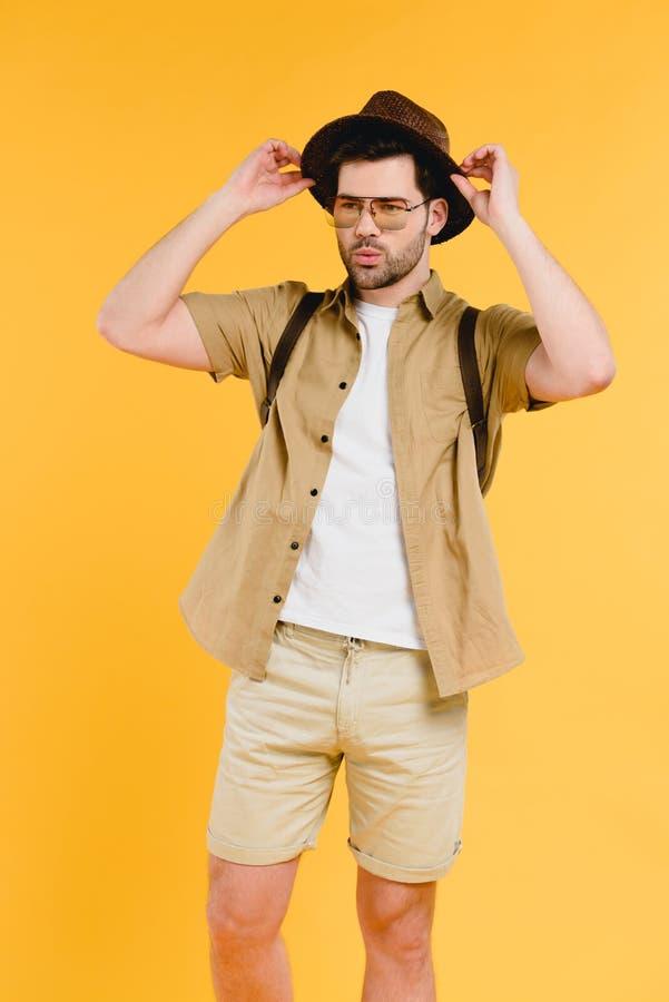 portrait de jeune homme beau dans des lunettes de soleil et de shorts ajustant le chapeau photo stock