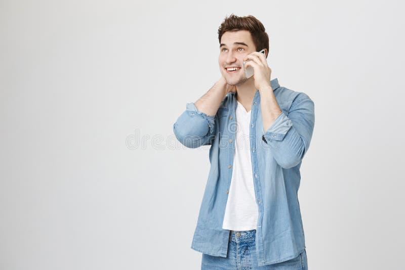 Portrait de jeune homme bel avec la coupe de cheveux élégante, chemise de port de denim, parlant du smartphone tout en touchant s photo stock
