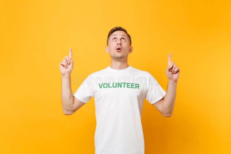 Portrait de jeune homme choqué étonné d'amusement dans le T-shirt blanc avec le volontaire écrit de titre de vert d'inscription d photo stock