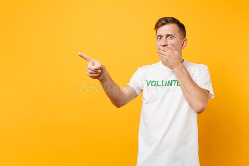 Portrait de jeune homme choqué étonné d'amusement dans le T-shirt blanc avec le volontaire écrit de titre de vert d'inscription d photo libre de droits
