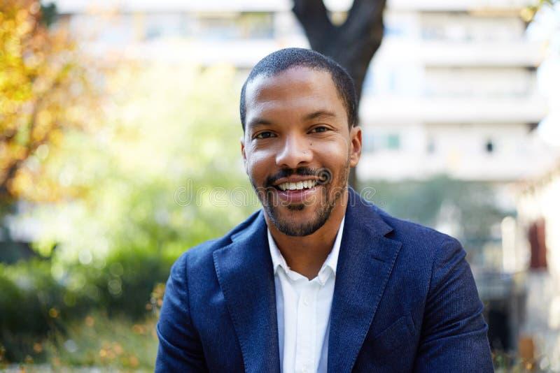Portrait de jeune homme d'affaires afro-américain sûr de sourire dans le tenue de soirée se reposant au parc de ville Fond brouil images libres de droits