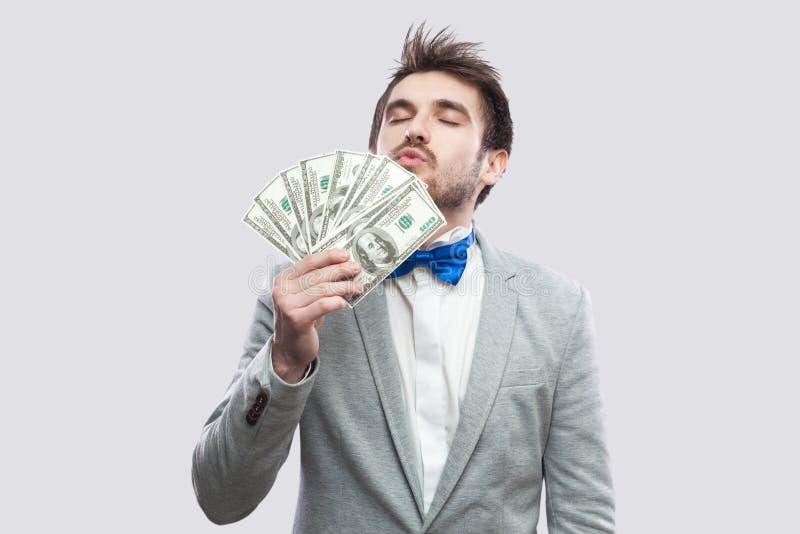 Portrait de jeune homme d'affaires attirant satisfaisant dans le manteau gris et la position bleue de noeud papillon, embrassant  photographie stock libre de droits
