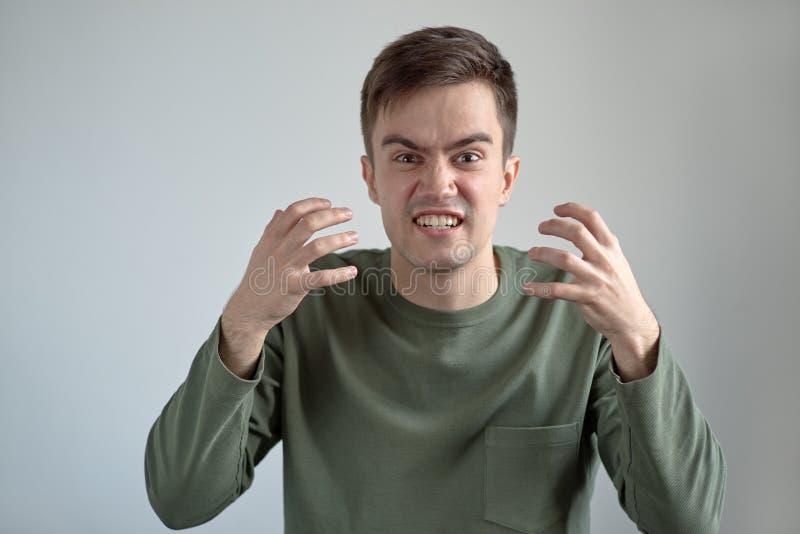 Portrait de jeune homme dans des vêtements sport avec un unh fâché furieux image stock