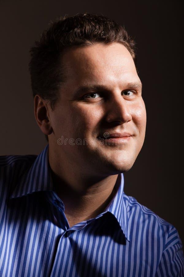 Portrait de jeune homme dans la chemise bleue sur gris-foncé image stock