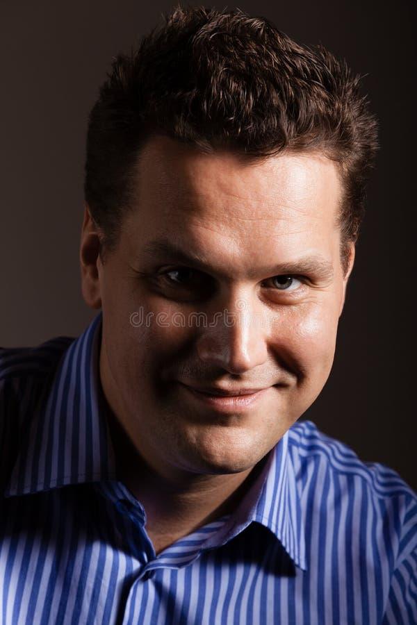 Portrait de jeune homme dans la chemise bleue sur gris-foncé photo stock