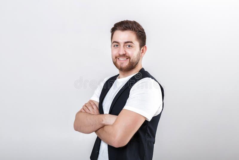 Portrait de jeune homme de sourire attirant dans la chemise blanche sur le fond gris photographie stock libre de droits