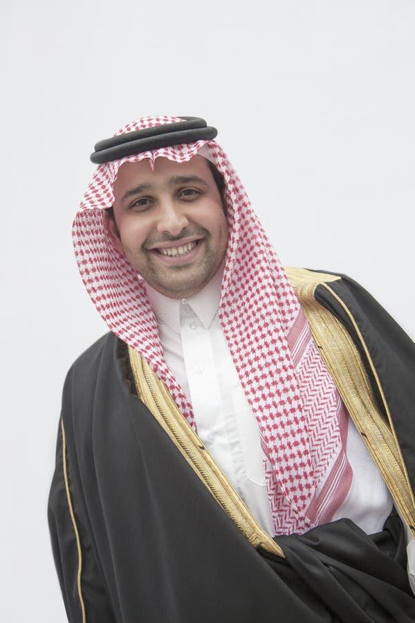 Portrait de jeune homme de sourire dans l'habillement et le Kaffiyeh arabes traditionnels, tir de studio photo stock