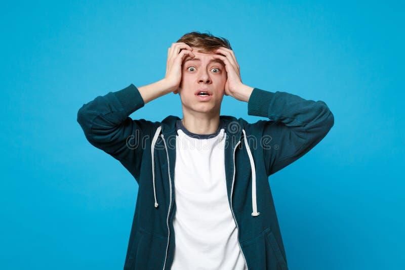 Portrait de jeune homme effrayé choqué dans des vêtements sport mettant la main sur la tête d'isolement sur le fond bleu de mur d photographie stock