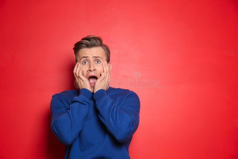 Portrait de jeune homme effrayé sur le fond de couleur photo libre de droits