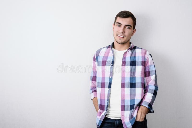 Portrait de jeune homme européen moderne dans la chemise de plaid rose et le T-shirt blanc contre le mur gris images libres de droits