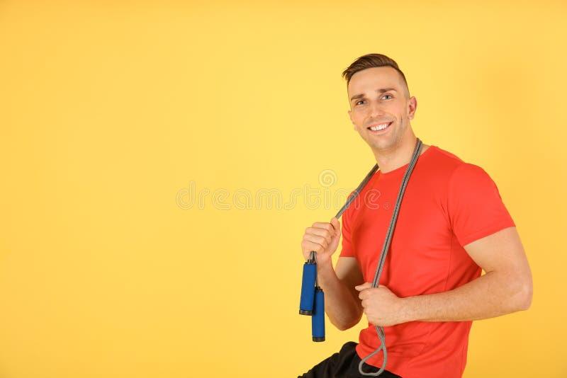 Portrait de jeune homme folâtre avec la corde de saut sur le fond de couleur images stock