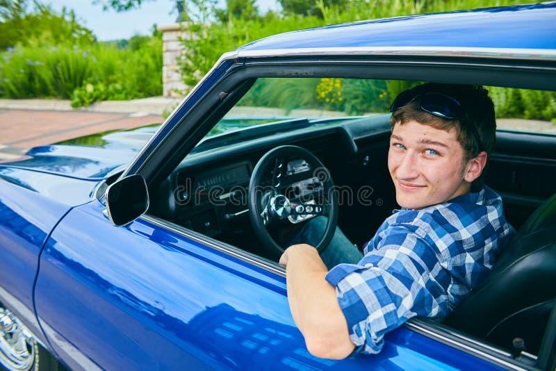 Portrait de jeune homme heureux conduisant la voiture bleue photographie stock libre de droits