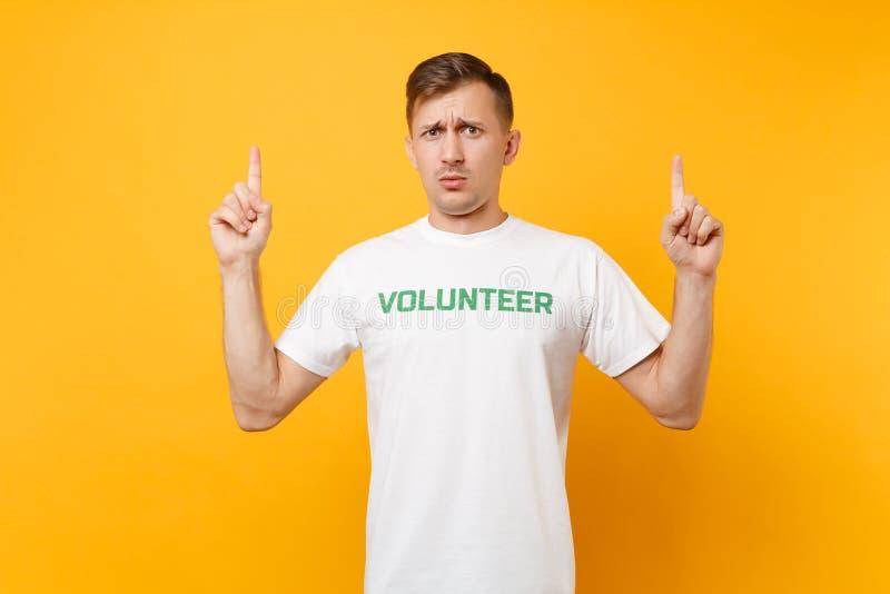 Portrait de jeune homme irrité contrarié dans le T-shirt blanc avec le volontaire écrit de titre de vert d'inscription d'isolemen photographie stock