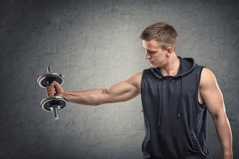 Portrait de jeune homme musculaire soulevant une haltère pour former son biceps photographie stock libre de droits