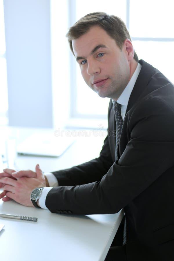 Portrait de jeune homme se reposant à son bureau dans le bureau photos stock
