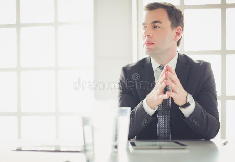Portrait de jeune homme se reposant à son bureau dans le bureau image stock
