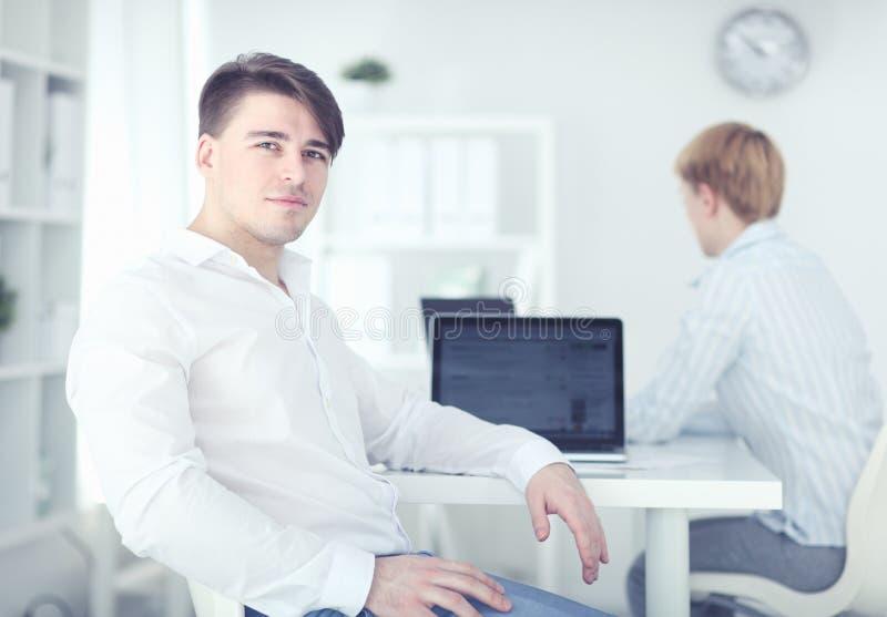 Portrait de jeune homme se reposant ? son bureau dans le bureau images libres de droits
