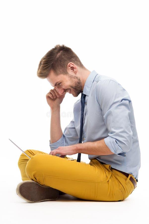 Portrait de jeune homme se reposant sur le plancher avec l'ordinateur portable images stock